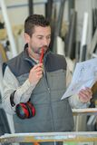 Workman checking plan overfulfilment at factory. Man stock photography