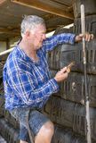 Workman checks mobile phone. A middle-aged workman takes a break as he leans up against a stack of buckets in a shed  to check his mobile phone Stock Photo