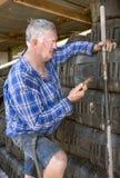 Workman checks mobile phone. Stock Photo