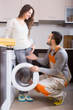 Workman and client near washing machine. Professional workman visiting customer for after-sales service. Focus on man Royalty Free Stock Images