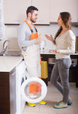 Workman and client near washing machine Stock Image