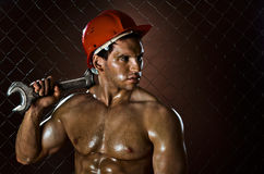 Workman. Closeup portrait  the beauty muscular workman, in red safety helmet  with big  adjustable wrench  in hand, sordid and sweaty Stock Photography