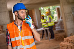 Workman communicating with walkie talkie Royalty Free Stock Images