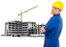 Workman in construction site. Workman in overalls and helmet by a construction site and blueprints Stock Photo