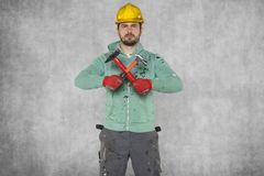 Workman crosses two hammers, ready to work. Protective helmet on the head Stock Photos