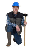 Workman crouching with hammer Stock Photos