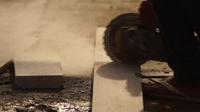 Workman cutting concrete blocks with angle circular grinder for house construction stock video
