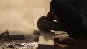 Workman cutting concrete blocks with angle circular grinder for house construction. Close up stock footage