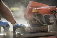 Workman cutting using an angle grinder. Workman cutting through a paving slab or brick in a cloud of dust using an angle grinder outdoors in a construction Royalty Free Stock Image