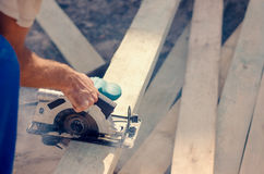 Workman cutting a wooden beam Royalty Free Stock Photo