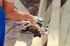 Workman cutting a wooden beam Royalty Free Stock Image