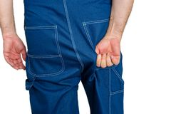 Workman in denim dungarees tugging at the fabric. Over his backside to alleviate a discomfort in a close up view of his hand Royalty Free Stock Photo