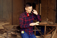 Workman dressed in the chekered shirt talking the phone and looking at the sawed wooden blanks at the sawmill. Royalty Free Stock Photography