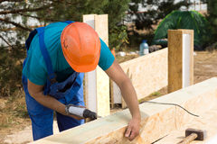 Workman drilling a hole in a wooden beam Royalty Free Stock Images