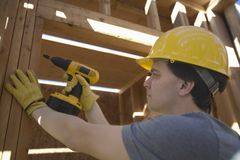 Workman Drilling On A Wooden Beam At Site Stock Photos