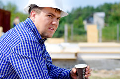 Workman drinking coffee in his hardhat Royalty Free Stock Photography