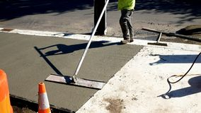Workman finishes and smooths concrete surface on new sidewalk royalty free stock images