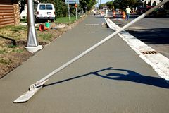 Workman finishes and smooths concrete surface on new sidewalk stock photos