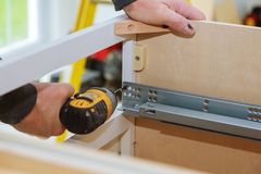 A workman fixing cabinet with screwdriver in kitchen. Kitchen cabinets Royalty Free Stock Photo