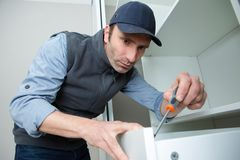Workman fixing kitchen drawer with screwdriver. Handyman royalty free stock photos