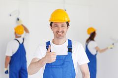 Workman gives thumbs up. In front of two painters Stock Photo