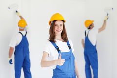 Workman gives thumbs up. In front of two painters Stock Photos