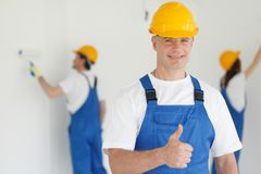 Workman gives thumbs up. In front of two painters Stock Image