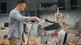 Workman in goggles using air compressor to blow sawdust from circular saw. Workman in protective goggles is using air compressor to blow sawdust from circular stock footage