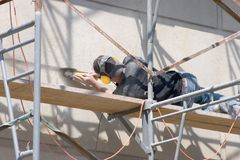 Workman Grinding Wall_7895-1S. Workman Laying on Scaffolding Grinding Concrete Wall Stock Image