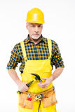 Workman in hard hat. Mature workman in hard hat holding hammer and looking at camera on white Stock Image