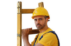 Workman in a hardhat carrying a ladder Royalty Free Stock Photography