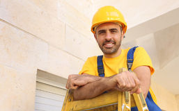 Workman in a hardhat carrying a ladder Royalty Free Stock Image