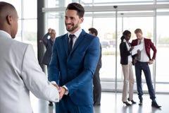 Workman heartily welcome black man Stock Photos