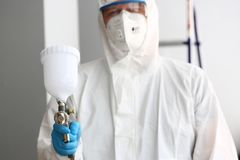 Workman hold in hand sprayer wearing protective suit stock photos