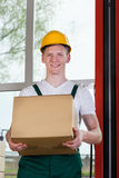 Workman holding a cardboard box. Portrait of a workman holding a cardboard box at warehouse Stock Image