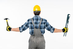 Workman holding hammer and pipe wrench Stock Photo