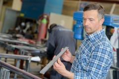 Workman holding length of metal stock photos