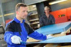 Workman holding sheet metal Stock Photos