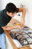 Workman Installing Gas Cooker In New Kitchen royalty free stock photos