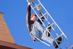 Workman installing HDTV digital antenna. On a house stock image