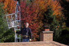 Workman installing HDTV digital antenna. On a house royalty free stock images