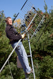 Workman installing HDTV digital antenna. On a house stock images
