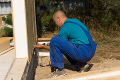 Workman installing insulated walls Stock Photo
