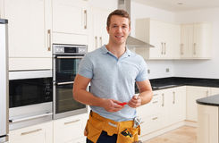 Workman Installing Luxury Fitted Kitchen Royalty Free Stock Image