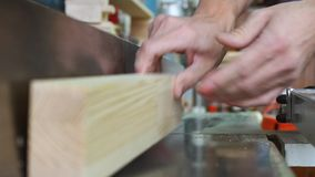 Workman in joinery workshop. Man using drill press to drill a hole into a piece of wood stock footage