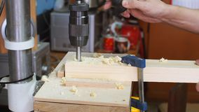 Workman in joinery workshop. Man using drill press to drill a hole into a piece of wood stock video footage