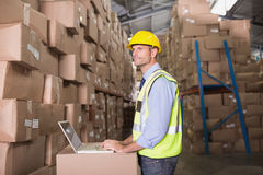 Workman with laptop at warehouse Stock Image