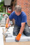 Workman laying new paving stones for a patio. Stock Photo