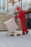 Workman lifting box on pallet. Middle aged workman in hard hat lifting cellophane wrapped box on wooden pallet in warehouse, stacked goods in background Royalty Free Stock Photography