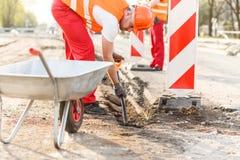 Workman loading a wheelbaroow Royalty Free Stock Image